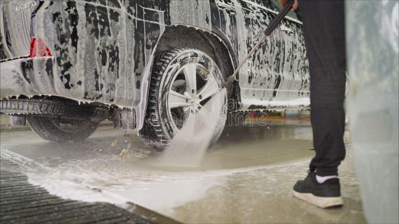 Колеса сплава моя автомобиля работника человека на мойке Мойка моет автомобиль на мойке стоковое фото rf