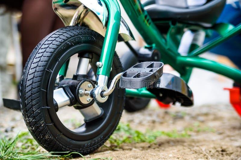 Колесо зеленого конца трицикла ` s детей стоковые фотографии rf