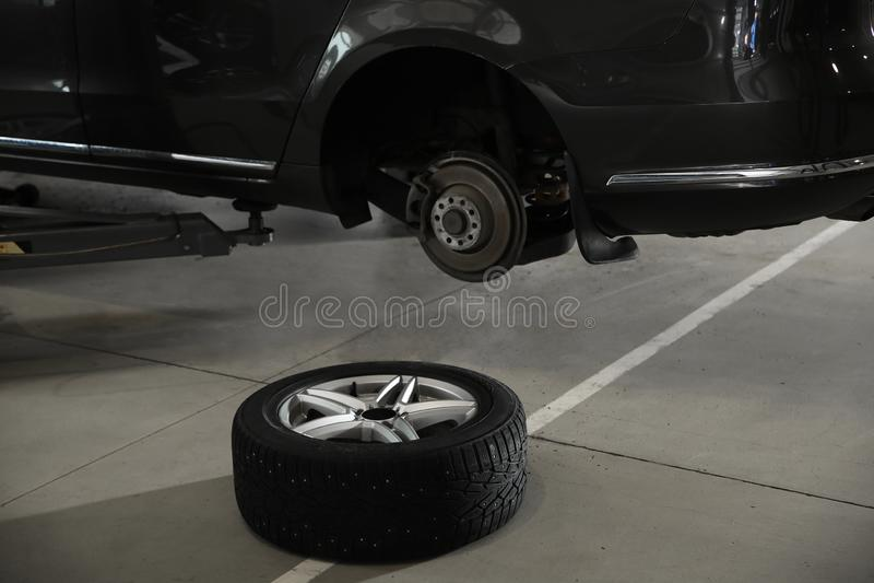 Колесо около поднятого автомобиля на ремонтной мастерской автомобиля стоковое изображение