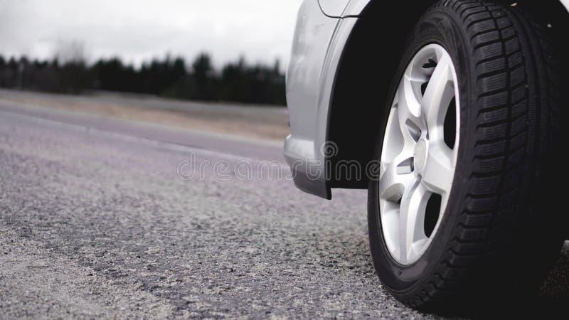 Колесо серебряного автомобиля на дороге Фото в серых тонах стоковая фотография