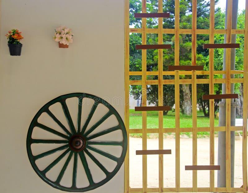 Колесо телеги на белой стене и деревянной решетке стоковые фото