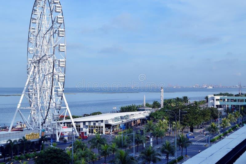 Колесо Ferris гиганта построенное вдоль залива океана стоковое фото