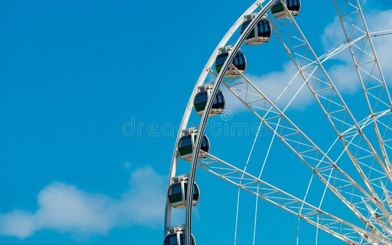 Колесо Ferris крупного плана современное против голубого неба и белых облаков Колесо Ferris на ярмарке для развлечений и воссозда стоковые фото
