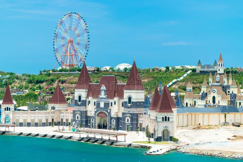Колесо Ferris на холме и замок сказки на пляже в парке атракционов стоковая фотография rf
