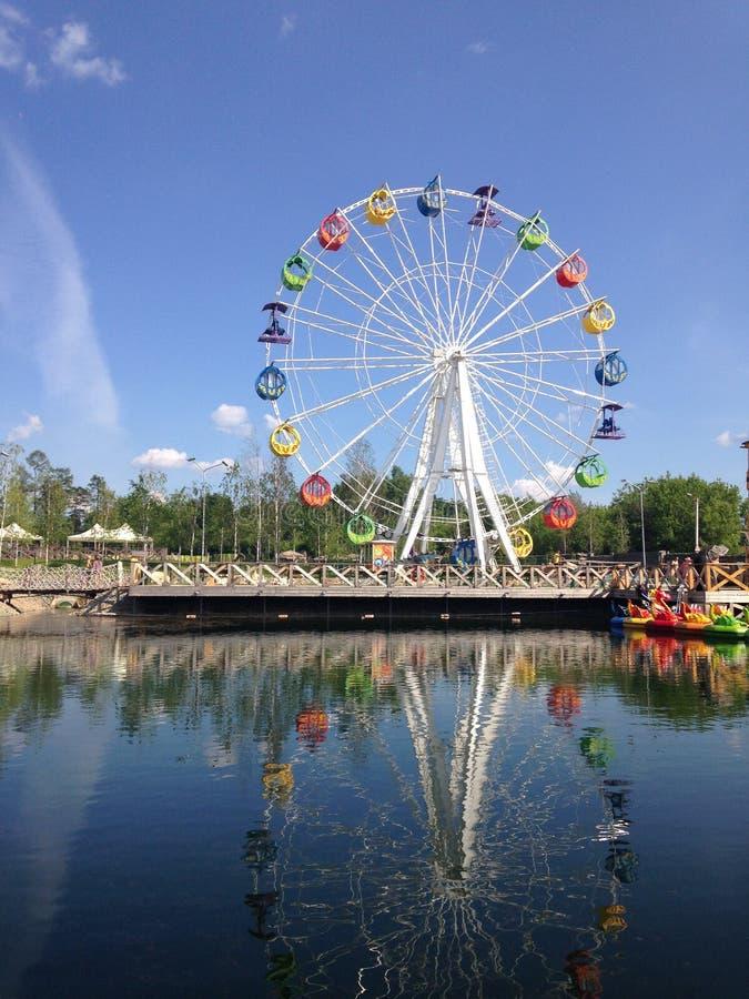 Колесо Ferris с пестроткаными будочками отраженными в воде дальше стоковое фото rf