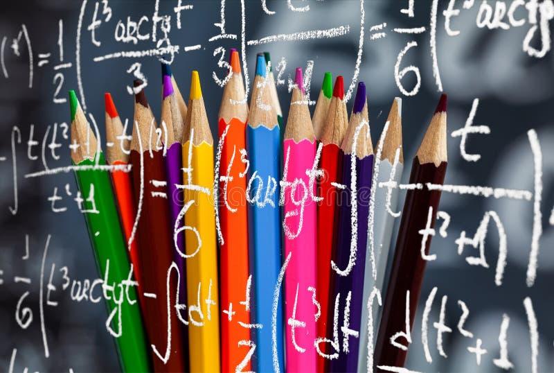 Коллаж задней части к предпосылке школы состоится к красочным карандашам и формулы математики написаны белым мелом дальше стоковое изображение rf