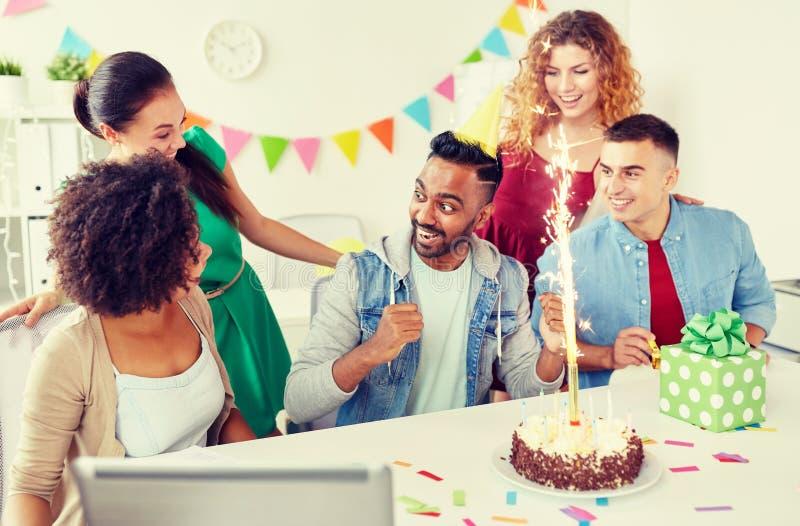 Коллега приветствию команды офиса на вечеринке по случаю дня рождения стоковые изображения rf