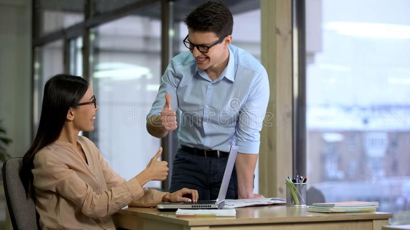 Коллеги агенства PR показывая большие пальцы руки вверх по смотреть один другого, удовлетворяемый с результатом стоковая фотография