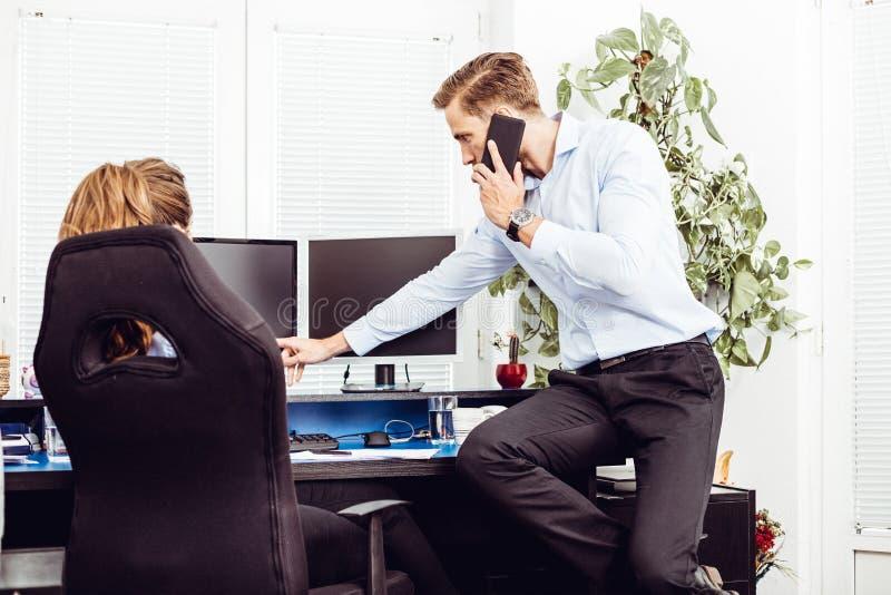Коллеги в офисе работая на настольном компьютере стоковые фото