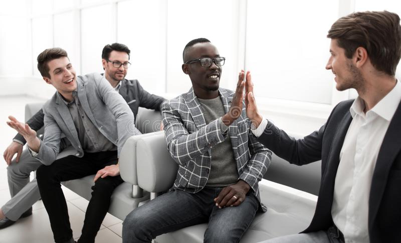 Коллеги дела давая одину другого высокие 5 пока сидящ в лобби офиса стоковые фото