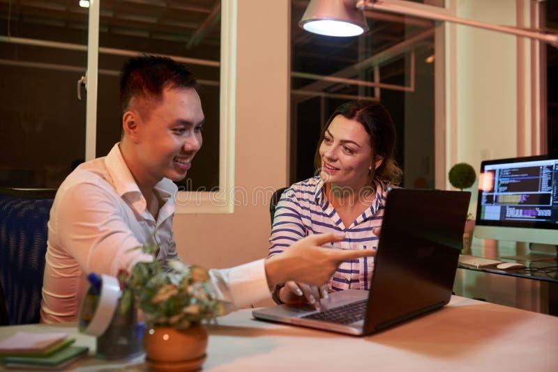 Коллеги дела используя ноутбук и работающ в команде стоковые изображения rf