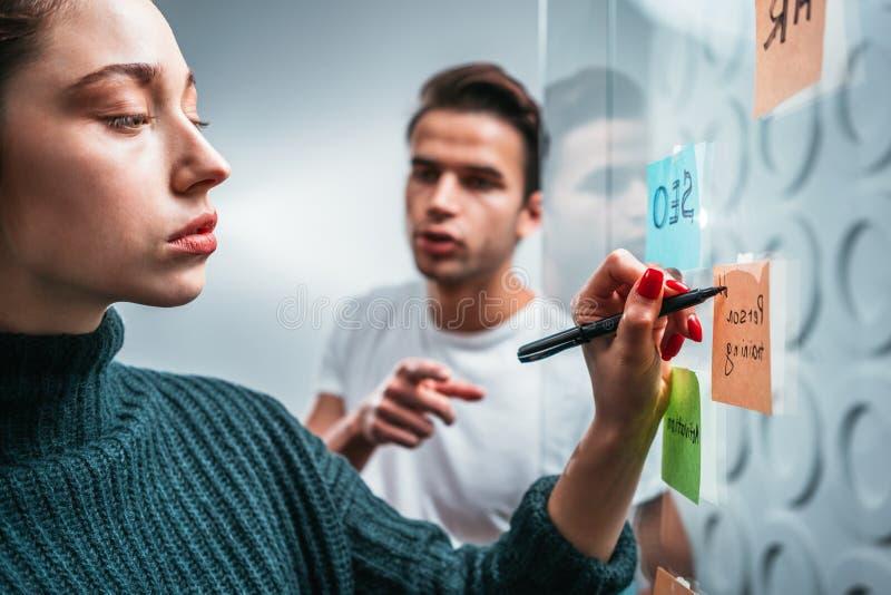 Коллеги дела обсуждая новые идеи и используя липкую стеклянную стену примечания стоковая фотография