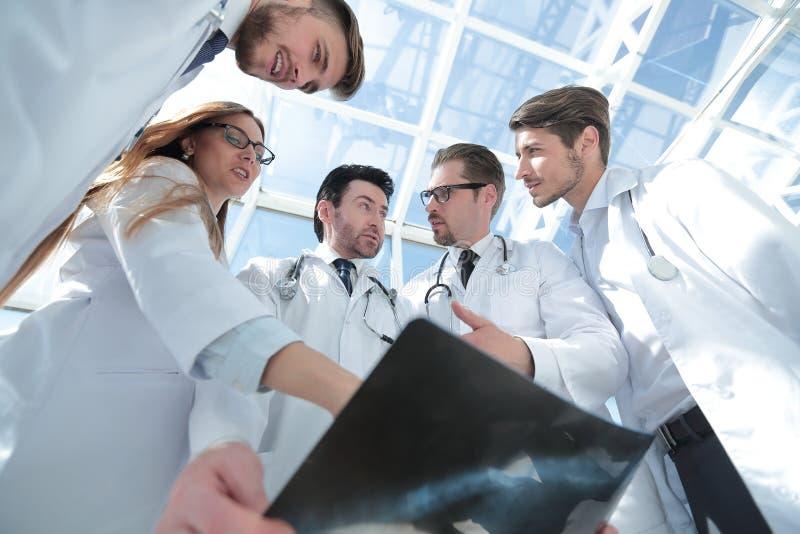 Коллеги докторов смотрят рентгеновский снимок пациента стоковое фото rf
