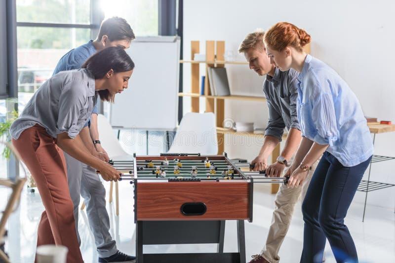 Коллеги играя футбол таблицы стоковые изображения rf