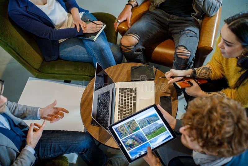 Коллеги и клиенты говоря стратегию с ноутбуком и планшетом Взгляд сверху Группа в составе многонациональные люди имея команду дел стоковая фотография rf