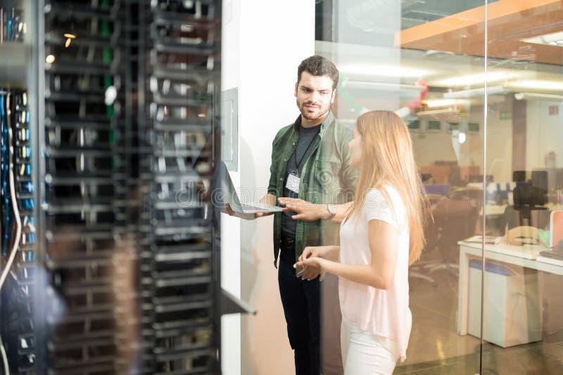 Коллеги обсуждая в комнате сервера офиса стоковое изображение rf