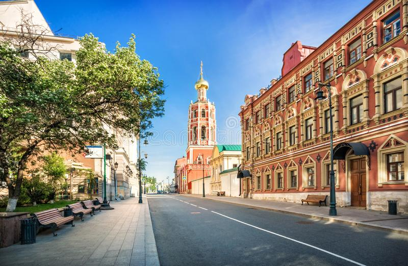 The bell tower of the Petrovsky Monastery in Moscow. And benches under the trees on a sunny summer morning royalty free stock photo
