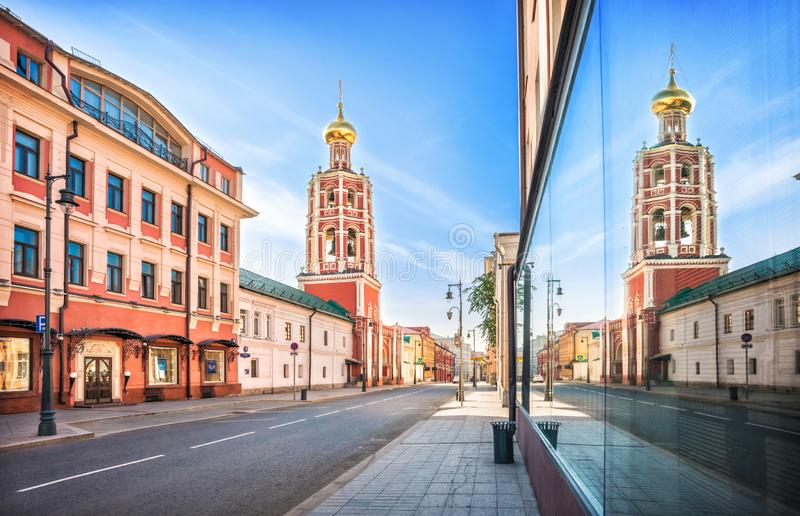The bell tower of the Petrovsky Monastery. In Moscow and its reflection in the glass of the window opposite stock photography