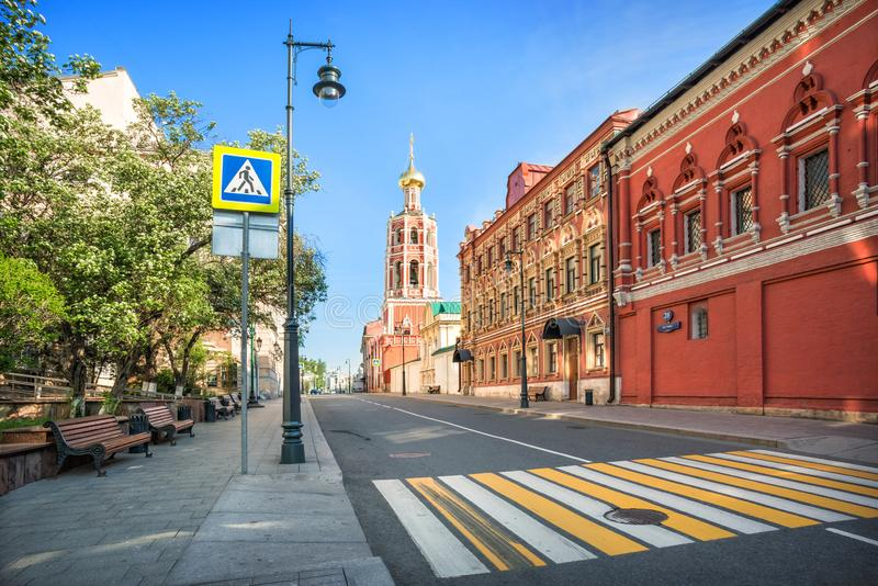 The bell tower of the Petrovsky Monastery. In Moscow and benches under the trees on a sunny summer morning royalty free stock images