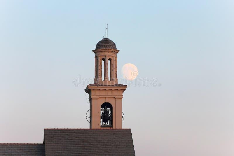 Колокольня церков на сумраке с большими концом/колоколом луны к стоковые изображения