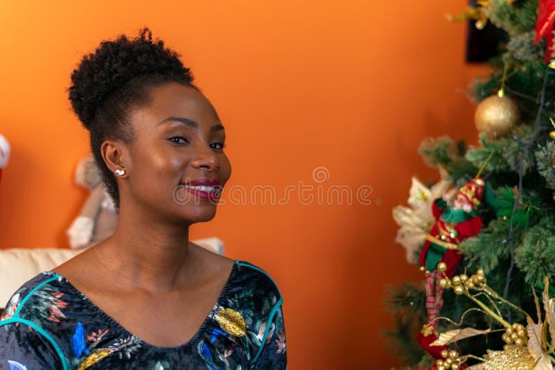 Колумбийская женщина африканского происхождения, сидящая на диване рядом с рождественской елкой, улыбается счастливо стоковые изображения