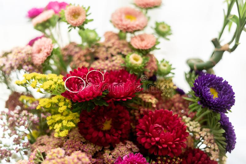 2 кольца золота жениха и невеста поверх цветка красочного букета цветков с белой предпосылкой стоковое изображение rf