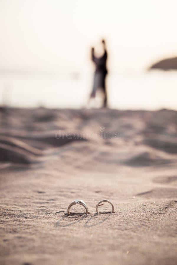 кольца на пляже с женихом и невеста на предпосылке стоковое изображение rf