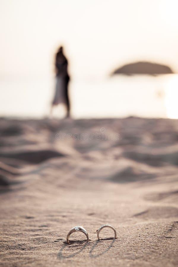 кольца на пляже с женихом и невеста на предпосылке стоковая фотография