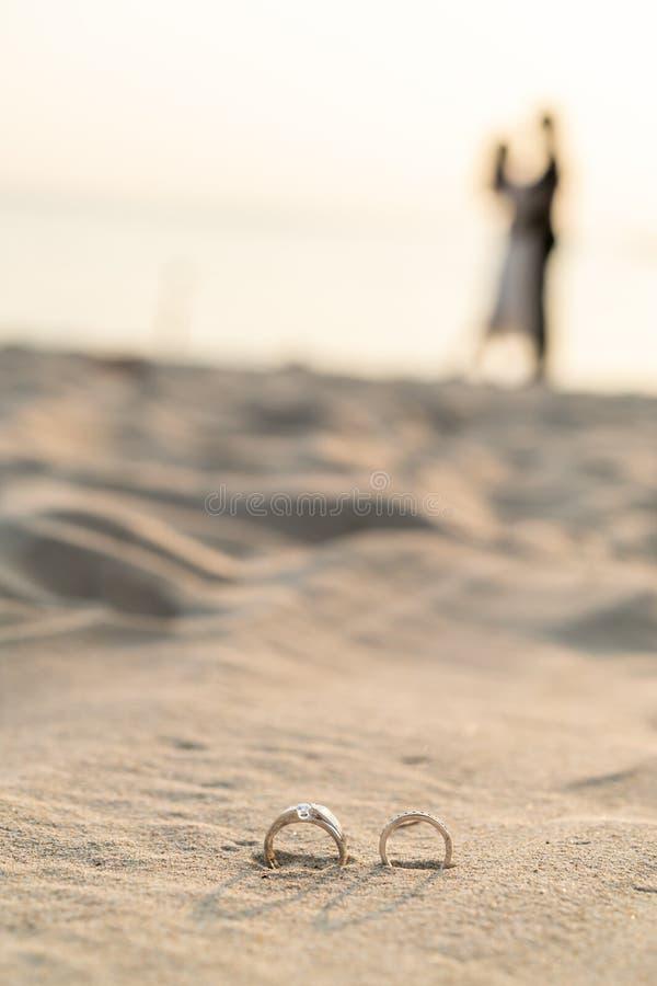 кольца на пляже с женихом и невеста на предпосылке стоковые изображения