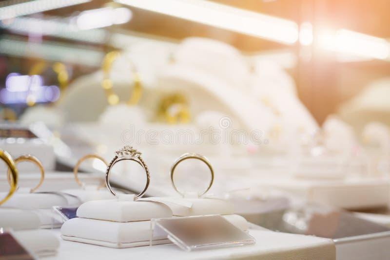 Кольца с бриллиантом и ожерелья ювелирных изделий показывают в роскошном магазине розничной торговли стоковое фото rf