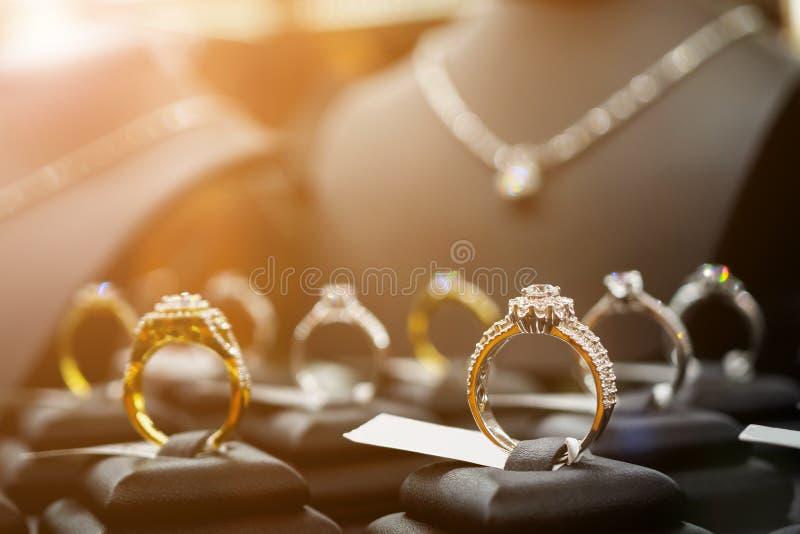 Кольца с бриллиантом и ожерелья ювелирных изделий показывают в роскошном магазине розничной торговли стоковые изображения rf