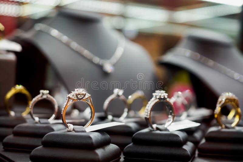Кольца с бриллиантом и ожерелья ювелирных изделий показывают в роскошном магазине розничной торговли стоковая фотография