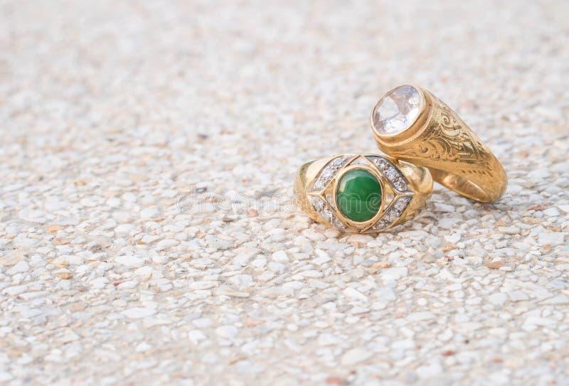 Кольца с бриллиантом крупного плана старые на запачканной каменной предпосылке пола стоковая фотография