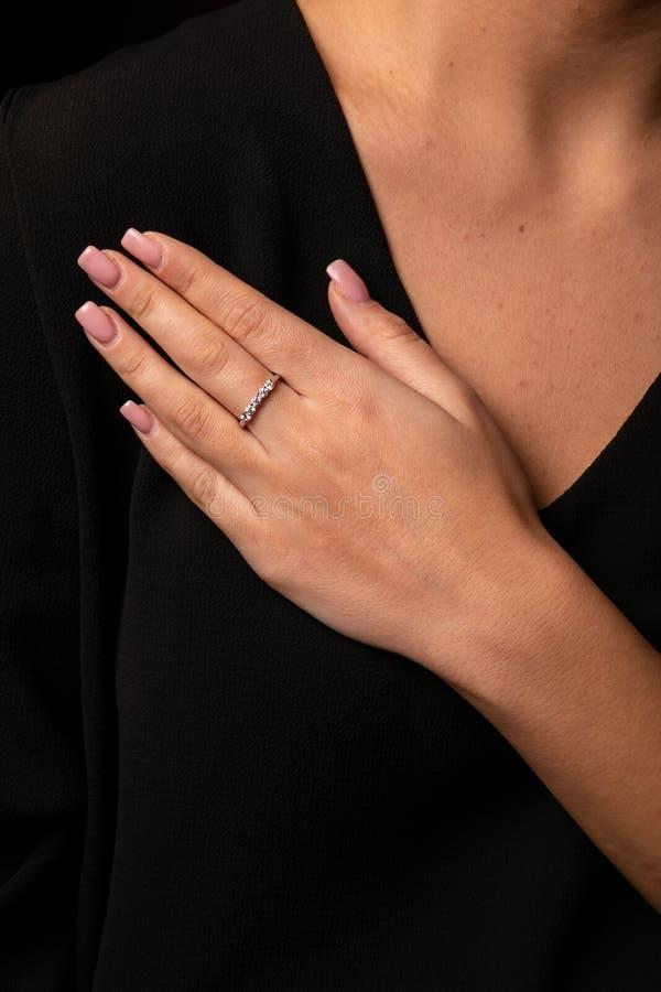 Кольцо диамантов женщин серебряное с краем на пальце, на черной предпо стоковые фотографии rf