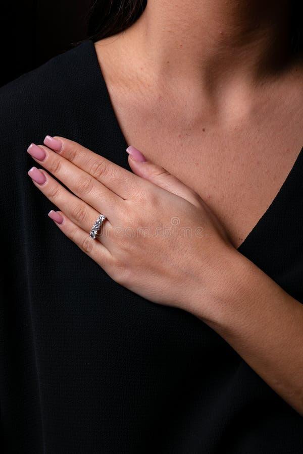Кольцо диамантов женщин серебряное с краем на пальце, на черной предпо стоковая фотография