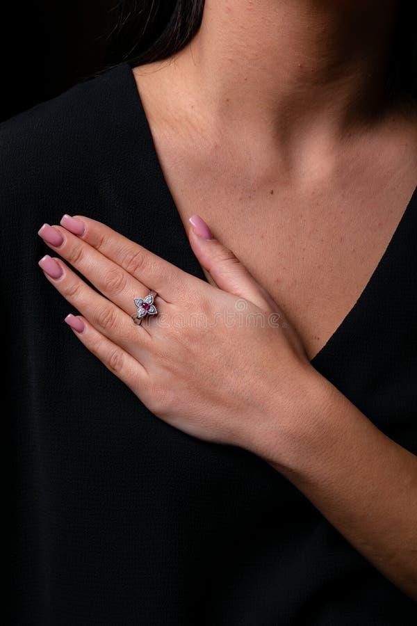 Кольцо женщин серебряное в форме цветка с красным камнем в середине на стоковые изображения rf