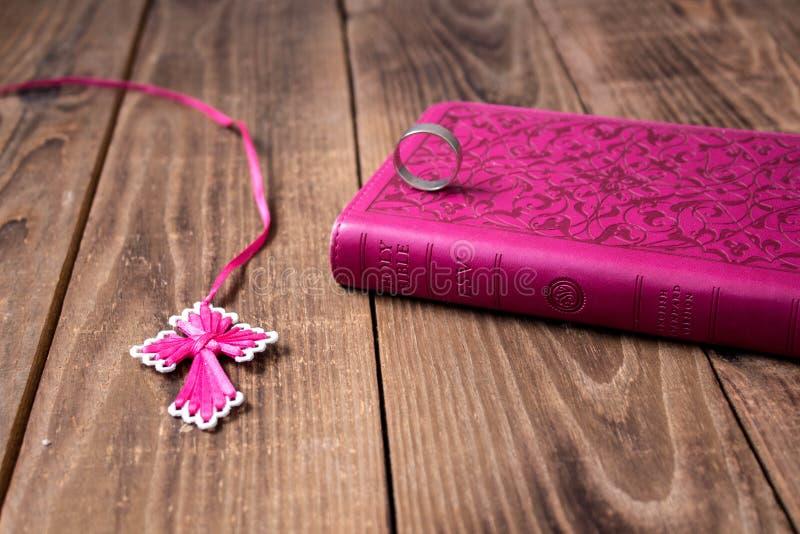 Кольцо на библии и крест на деревянной предпосылке стоковые фото