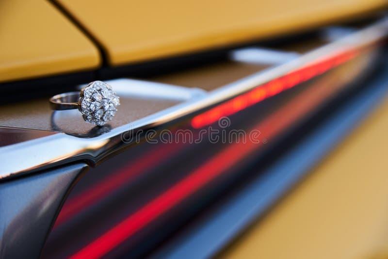 Кольцо с бриллиантом лежит на фаре автомобиля спорт стоковые фото