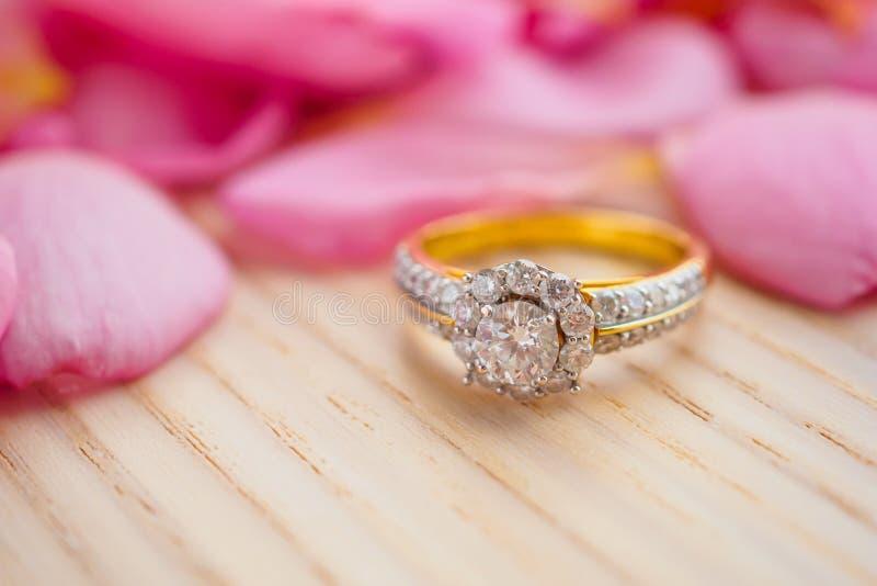 Кольцо с бриллиантом ювелирных изделий на деревянной таблице с красивой розовой предпосылкой лепестка розы стоковое фото rf