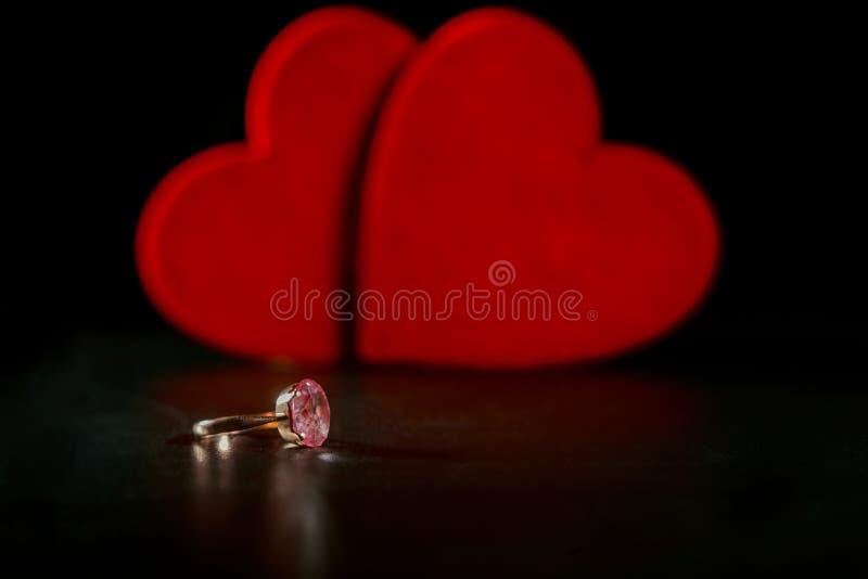 Кольцо с камнем на предпосылке 2 декоративных сердец стоковые фотографии rf