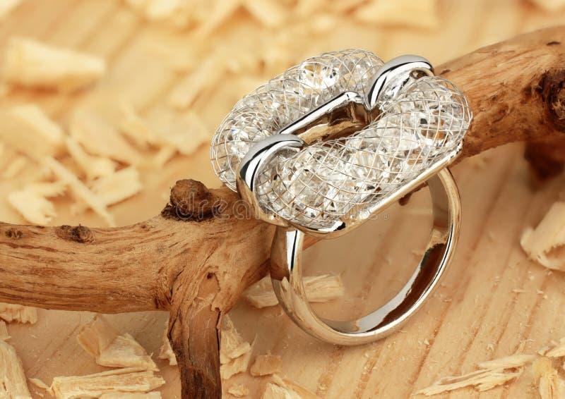 Кольцо ювелирных изделий с диамантами, на деревянной предпосылке опил стоковое изображение