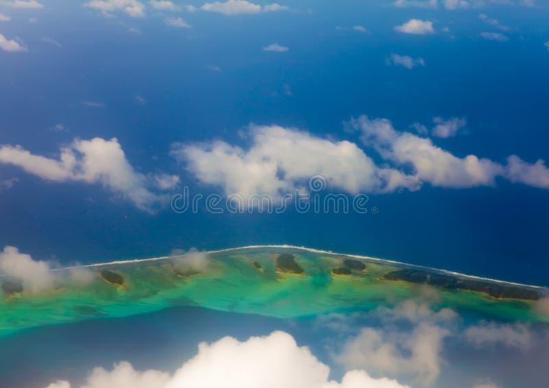 Кольцо atoll на океане видимо через облака. стоковые фотографии rf