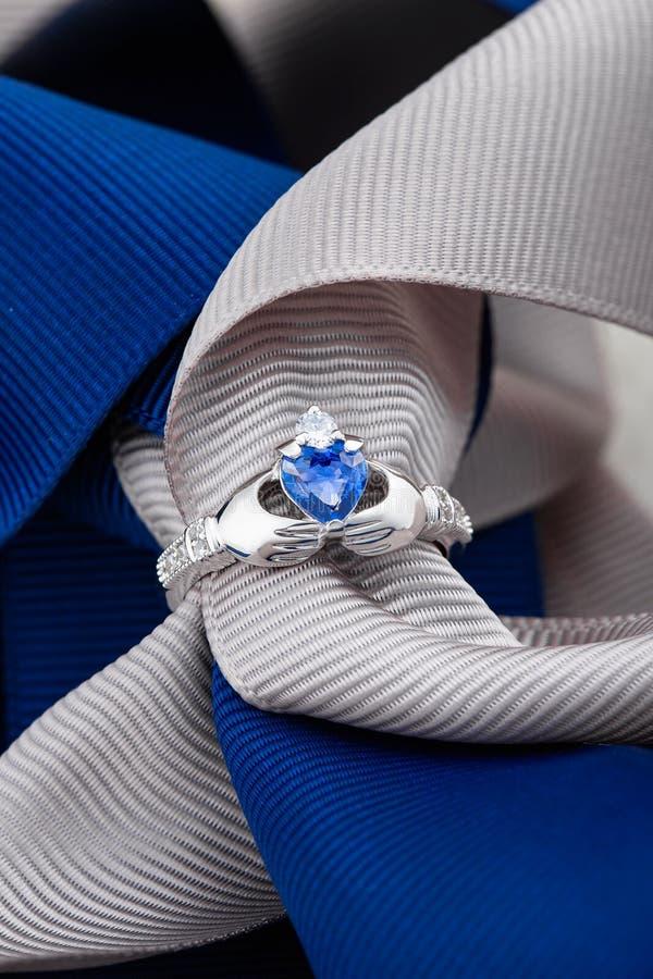 Кольцо Claddagh с голубым топазом на предпосылке ленты стоковые фотографии rf