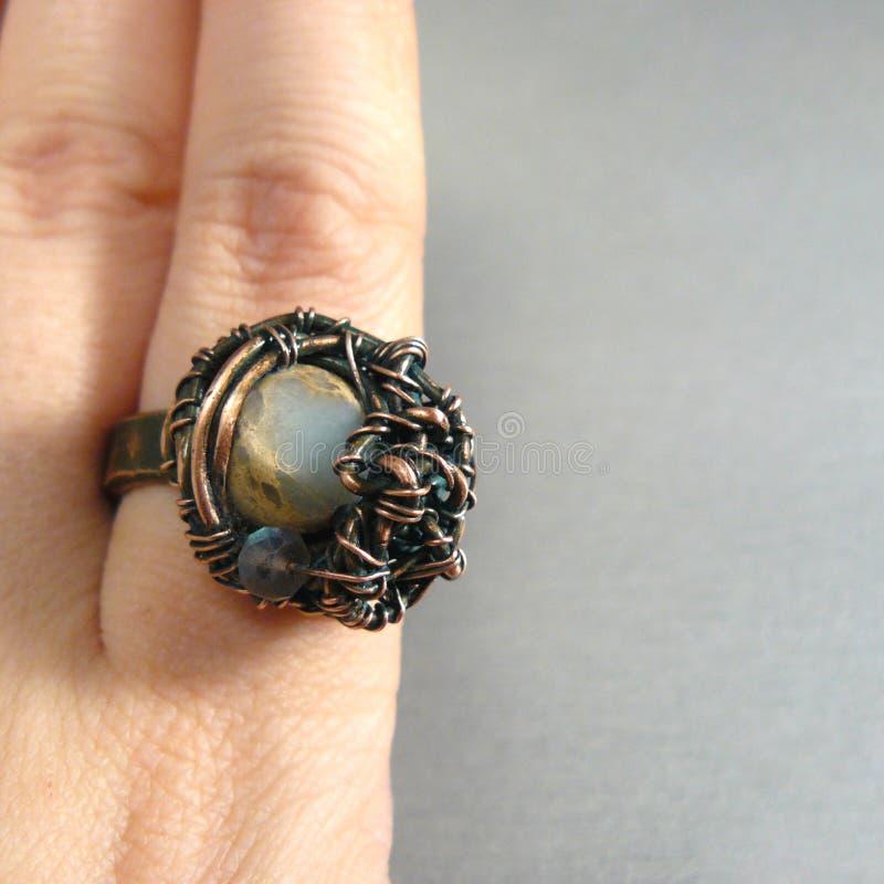 Кольцо Handmade uniq большое зверское на руке на серой предпосылке стоковая фотография