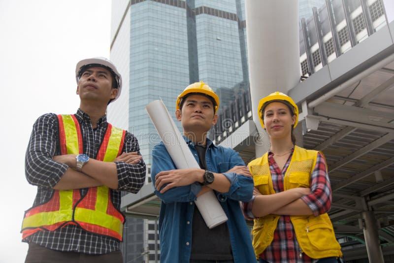 Команда архитектур стоя на строительной площадке смотря p стоковые фотографии rf