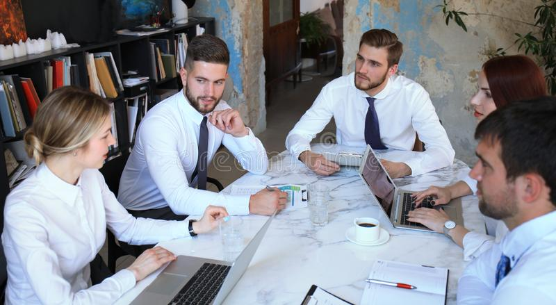 Команда бизнесменов имея обсуждение на таблице в творческом офисе стоковые фотографии rf