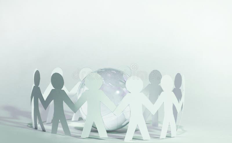 Команда бумажных людей куклы держа руки вокруг планеты стоковые изображения rf