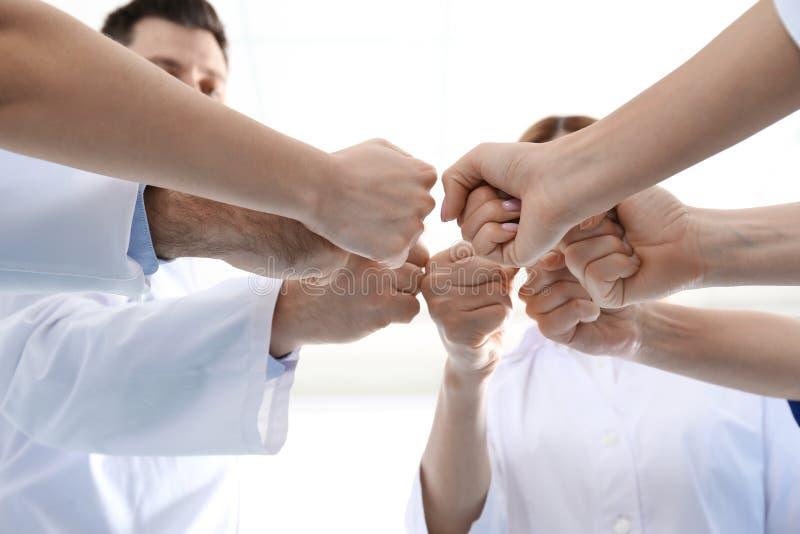 Команда врачей кладя руки совместно на светлую предпосылку Концепция единства стоковое изображение rf