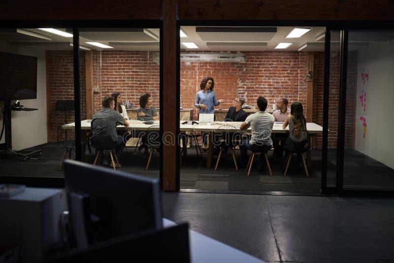Команда дела имея ночное встречая усаживание вокруг таблицы зала заседаний правления стоковая фотография rf