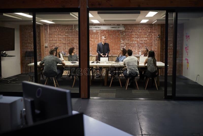Команда дела имея ночное встречая усаживание вокруг таблицы зала заседаний правления стоковые изображения rf